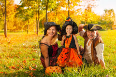 Family in Halloween costumes sitting on the grass. With pumpkin outside during beautiful sunny autumn day royalty free stock photos