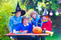 Family on Halloween. Happy young familly, parents with two children, teenager boy and funny toddler girl wearing witch costume and hat celebrating Halloween and Stock Photo