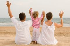 Family with hand up are looking the ocean Stock Photo