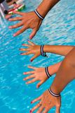 Family hands with all inclusive bracelets by resort swimming pool. Parents and children enjoying summer vacation in hotel. Holidays, travel destination, fun stock image