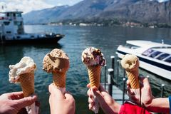 Family hands holding cones of Gelato, Italian ice-cream with blur background of a landscape view of Lake Como in Italy. Concept of family vacation and royalty free stock images