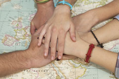Family hands together over a world map. Team concept. Stock Images