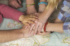 Family hands together over a world map. Team concept. Royalty Free Stock Image