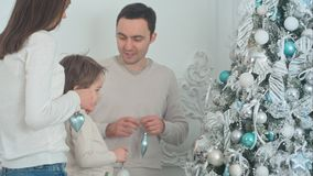 Family hanging decorations on a Christmas tree at home stock photography