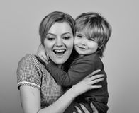 Family happiness concept. Mother hugs son on pink background. Woman and little boy. With cheerful smiles. Mom and child spend time together Stock Photography