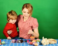 Family happiness and Easter celebration concept. Woman and little boy. With cheerful smiles. Mother holds son on green background. Mom and child spend time royalty free stock images