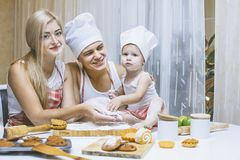 Family, happy daughter with dad and mom in home kitchen laughing. And preparing food together, with love royalty free stock photo