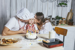 Family, happy daughter with mom and dad at home in the kitchen l Stock Images