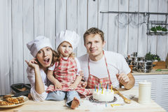 Family, happy daughter with mom and dad at home in the kitchen l Royalty Free Stock Images