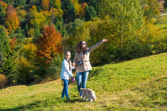 Family. Happy mother and daughter resting in the autumn forest, mother pointing at something Royalty Free Stock Image