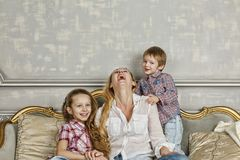 Family, happy, Mother`s Day, Family Day, Mom, Happy family, chil. Happy family. Smiling children are having fun with their Mom on the couch at home. Mother`s Day royalty free stock images