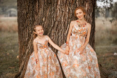 Family happy outdoors. The Mother and daughter in matching dresses stock image