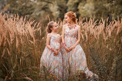 Family happy outdoors. The Mother and daughter in matching dresses stock photography