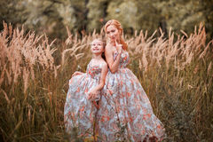 Family happy outdoors. The Mother and daughter in matching dresses royalty free stock image