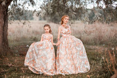 Family happy outdoors. The Mother and daughter in matching dresses stock photo