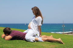 The family is happy. Young couple relaxing on the grass by the sea. Charming young women is pregnant. A lovely summer day, the family is happy Stock Photography