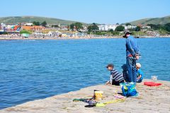 Family on harbour wall, Swanage. Royalty Free Stock Images