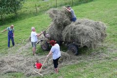 Retro scene family is harvesting hay before the rain is coming, Bohemia, Czech republic Stock Photos