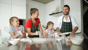 Family Has Fun With Each Other Playing With Flour. Happy Parents in Aprons Help Kids Cooking. stock video