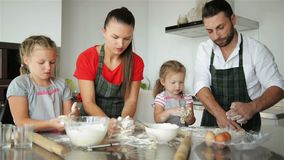 Family Has Fun With Each Other Playing With Flour. Happy Parents in Aprons Help Kids Cooking. stock footage