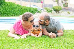 Family has fun at the green grass near pool during summer day.  Stock Photos