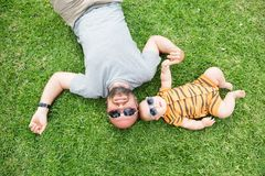 Family has fun at the green grass near pool during summer day.  Royalty Free Stock Photo