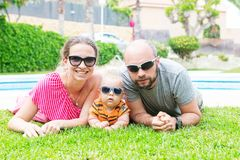 Family has fun at the green grass near pool during summer day.  Royalty Free Stock Photography