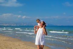 Family has fun at the seashore in summertime.  stock image