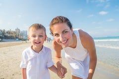 Family has fun at the seashore in summertime Stock Photos