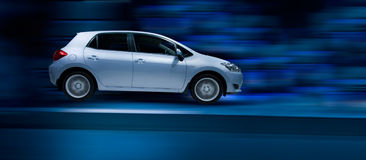 Family hatchback car. Driving fast with motion blur Stock Photo