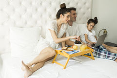 Family have breakfest on the bed Stock Photos
