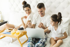 Family have breakfest on the bed Stock Images