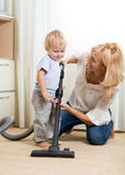 Family have fun with cleaning with hoover -. Family mother and child have a fun cleaning room with hoover - housework Royalty Free Stock Photography