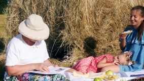 Family have a picnic in the meadow. Family with grandmother, mother and little daughter doing picnic outdoor with a melon in the meadow near the haystack stock footage