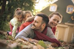 Family have play on backyard. Family have play on backyard , laying on fall leaves Royalty Free Stock Photo