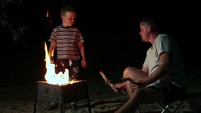 Family have a rest in camp at night near campfire stock video footage