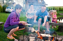 Family having a barbeque. With Father looking after the fire and the small children keeping at a safe distance from the flames and smoke Royalty Free Stock Images