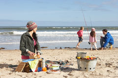 Family Having Barbeque On Winter Beach Stock Photo