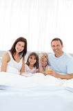 Family having breakfast on the bed Stock Image