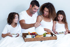 Family having breakfast in bed. At home Royalty Free Stock Photo