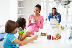 Family Having Breakfast In Kitchen Together stock images