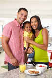 Family Having Breakfast In Kitchen Together Stock Photo