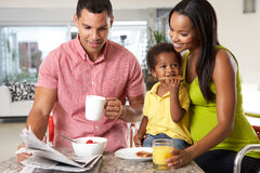 Family Having Breakfast In Kitchen Together. Smiling To Camera stock images