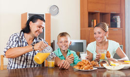 Family having breakfast with oranges juice in morning Stock Images