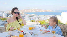 Family having breakfast at outdoor cafe with amazing view on Mykonos town. Adorable girl and mom drinking fresh juice stock footage