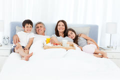 Family having breakfast in their bed Stock Photography