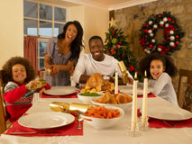 Family Having Christmas Dinner. Mixed race family having Christmas dinner stock photo