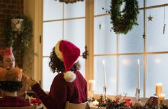 Family having a Christmas dinner by the window together Royalty Free Stock Photo