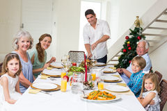 Family having Christmas meal at dining table. Portrait of father serving Christmas meal to family at dining table Stock Images