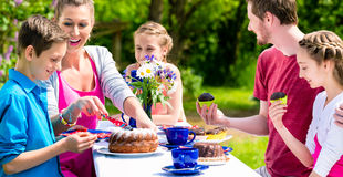 Family having coffee and cake in garden at house Stock Photo